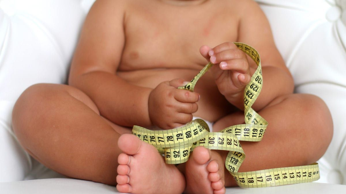 Obese Baby Holding a Tape Measure