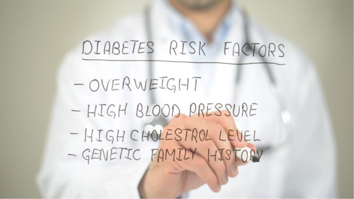 Doctor in Coat writing list of Diabetes Risks
